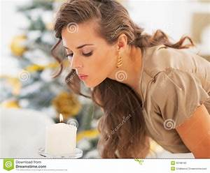 Young Woman Blowing Out Candle In Front Of Christmas Tree ...  Blowing