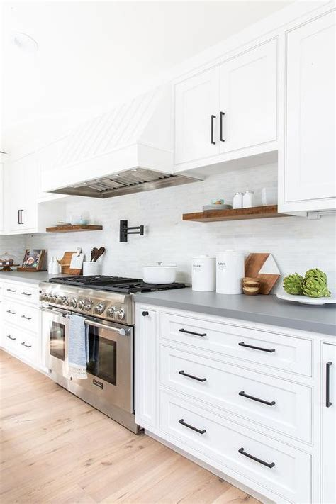 white kitchen cabinets with rubbed bronze hardware gray island with dishwasher and farm sink transitional 2261