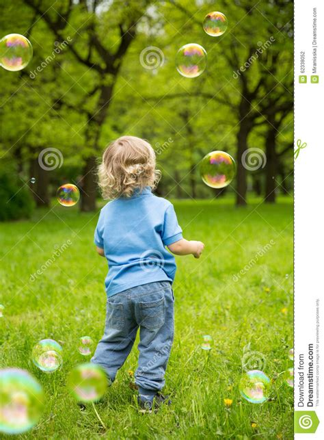 cute curly baby  soap bubbles children playing stock photo image