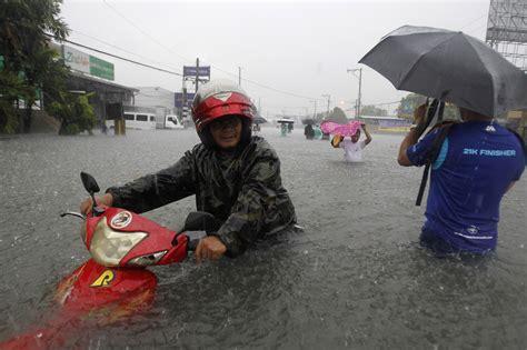 motorcycle rain heavy rain floods batter philippines
