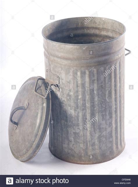 open corrugated metal garbage bin  lid leaning