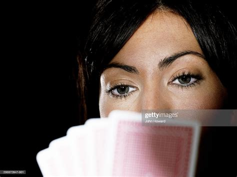 woman holding playing cards   face closeup high res