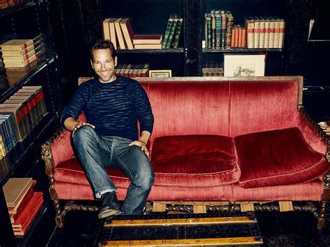 paul rudd actor smile sweater jeans sofa shelf books ...