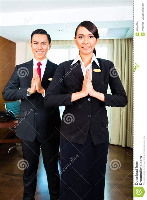 asian hotel staff greeting  hands put  stock