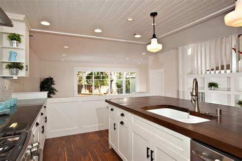 white kitchen  wood island carrara backsplash black