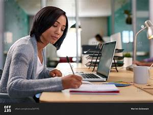 Office worker writing notes at desk stock photo - OFFSET