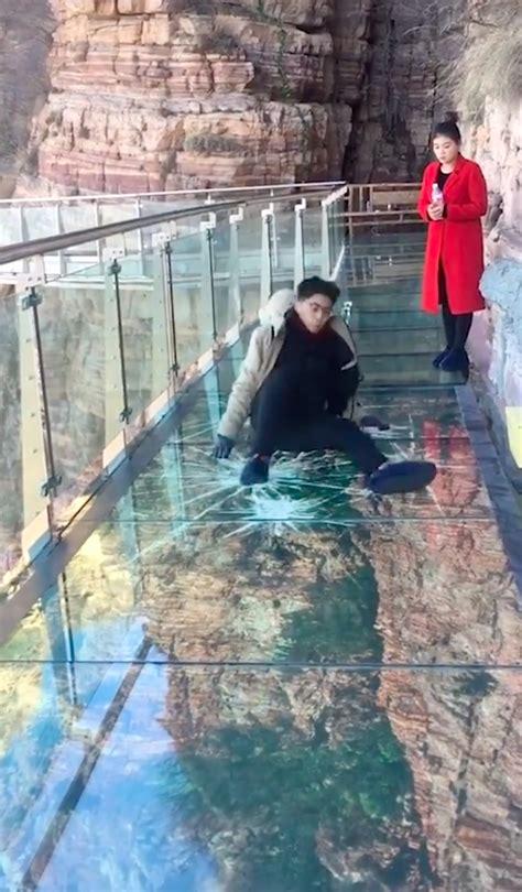 guy scrambles  glass walkway  floor cracks