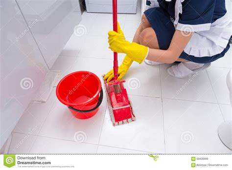 Bathroom Floor Cleaner by Housekeeper Fitting A Clean Cloth To A Mop Stock Image