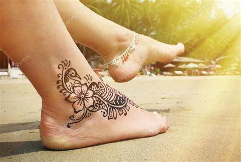 tatouage au henne sur le pied sur la plage photographie