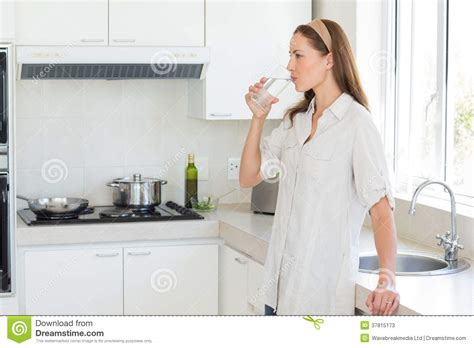 side view   woman drinking water  kitchen stock