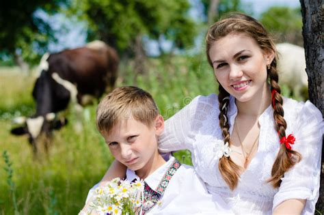 Teen Sister And Little Brother Sitting By Cow Herd Stock