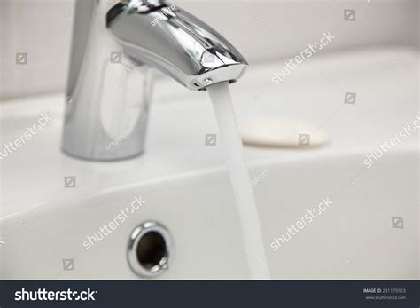 Water Tap Faucet With Flowing Water In A White Bathroom