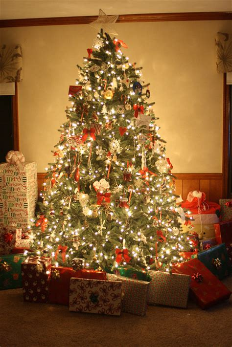 lit christmas tree with gifts pictures photos and images