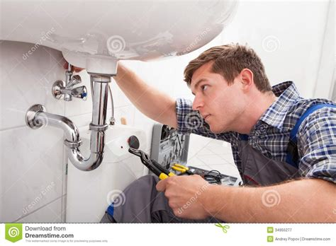 Young Plumber Fixing A Sink In Bathroom Stock Image