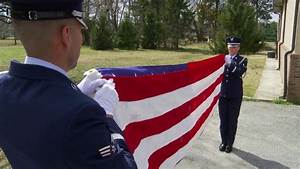 Soldiers from an honor guard perform a flag folding ...
