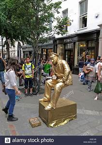 Street performer busker dressed in gold sitting on an ...