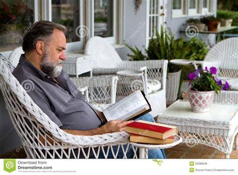 man reading bible  porch stock photo image