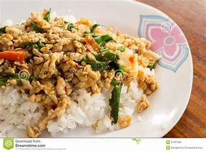 Fried Rice With Basil On A White Plate On A Wooden Table ...