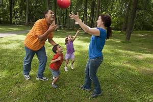 Parents with two young children play outside with a ...
