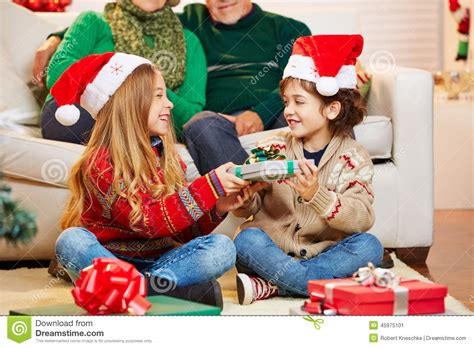 siblings giving gifts to each other at christmas stock