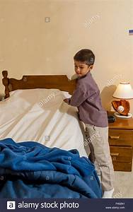 Young Korean/American boy making his bed. MR ©Myrleen ...