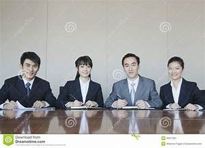 Four Young Business People Sitting In A Row At A ...