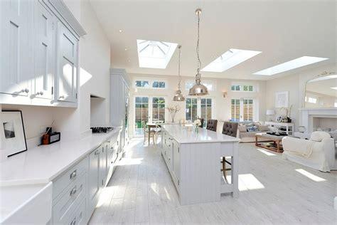 open plan white wood kitchen light wooden floor kitchen contemporary with black pendants long skylight light wooden floors