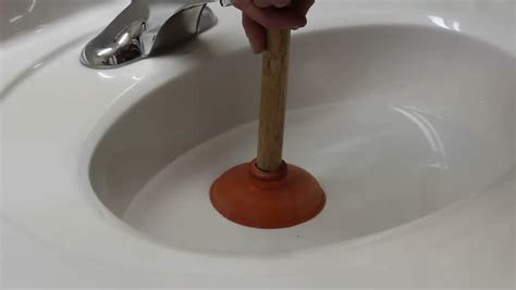 Unplugging A Sink With A Small Plunger Stock Footage Video