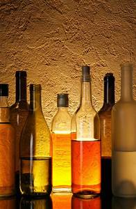 Lots bottles of alcohol drinks over textured background ...