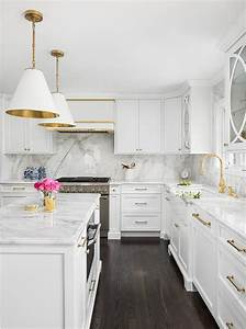 white and gold kitchen with polished marble slab
