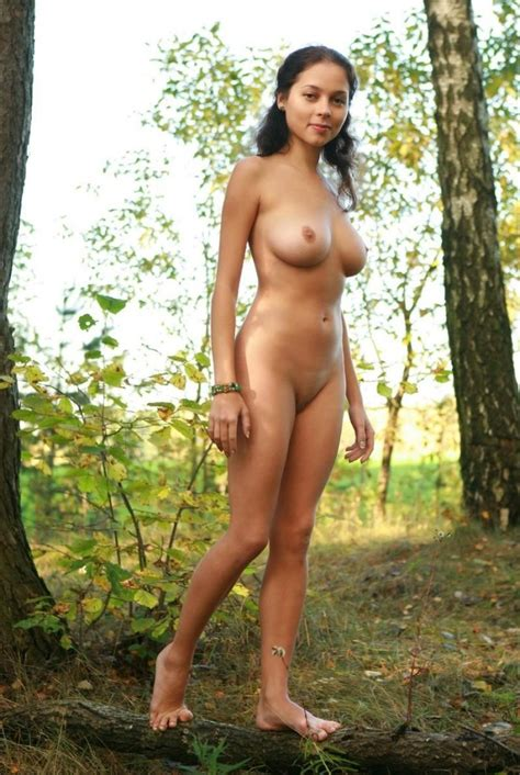 smiling brunette with huge boobs walks in the woods