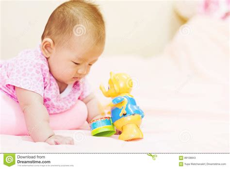 Newborn Baby Playing On Colorful Toy Stock Photo Image