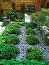 Slate chips are used to mulch pathways between plantings slate garden landscaping