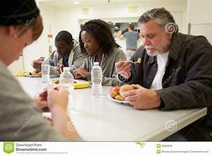 People Sitting At Table Eating Food In Homeless Shelter ...