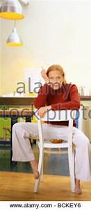 Woman sitting backward on a chair with denim skirt and ...