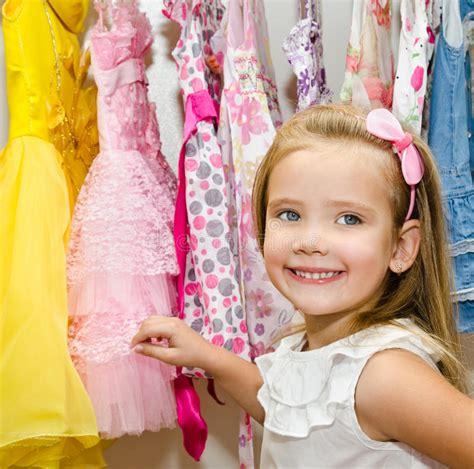 guardaroba abbigliamento la bambina sorridente sceglie un vestito dal guardaroba