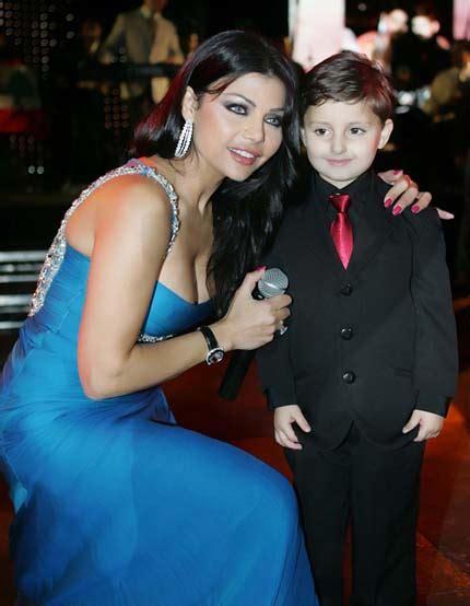 haifa wahbi during a concert wearing a glam baby blue dress with a boy fan