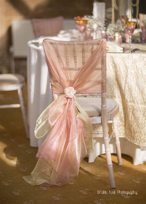 a limewash chiavari chair with a hand tied dusky pink and