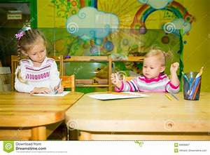 Two Little Kids Drawing With Colorful Pencils At The Table ...