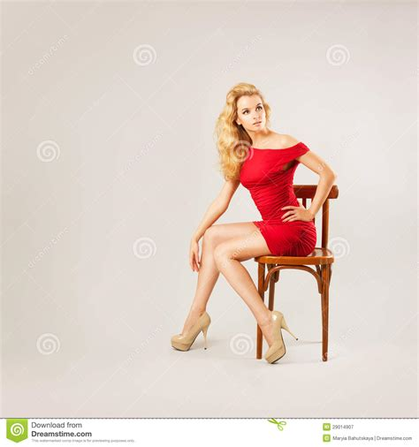 beautiful woman  red dress sitting   chair stock