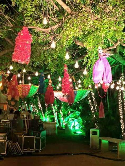 rajasthani puppets n umbrellas hanging from tree wedding