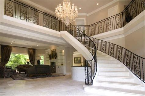 travertine sweeping staircase graces  story entry walk