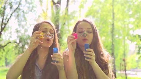 Beauty Teen Girls Having Fun Outdoors Beautiful Joyful Teenagers Laughing And Blowing Soap