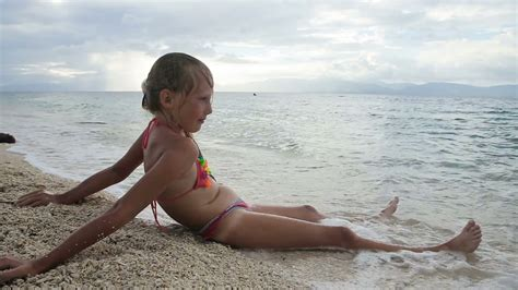 Young Girl Sitting On A Tropical Beach Watching The Seaa