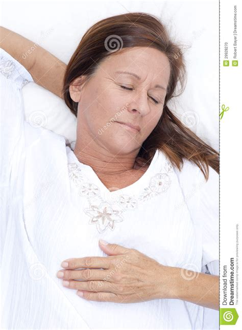 happy mature woman asleep  bed stock photo image