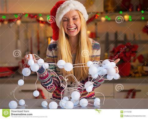Teenager Girl Untangling Christmas Lights Stock Photo