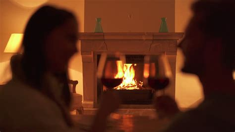 happy young couple sitting  fireplace  drinking