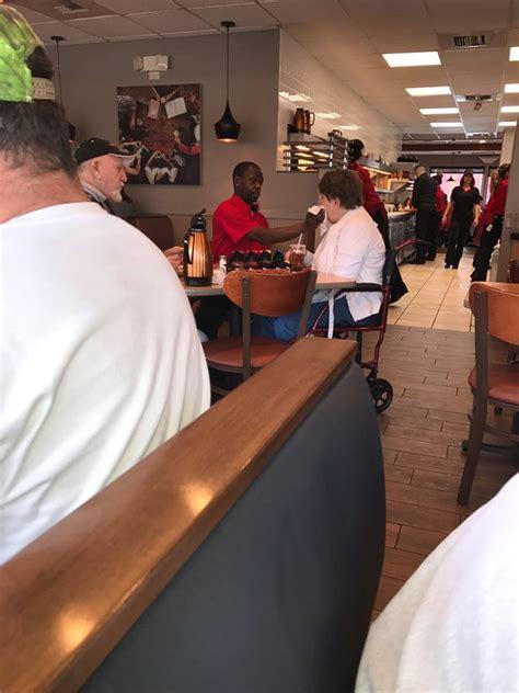 waiter feeds disabled woman   husband  enjoy