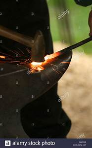 A blacksmith working red hot iron on an anvil Stock Photo ...