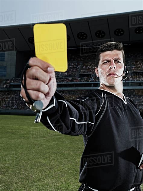 Card stock paper for signs, posters, notices, and other uses. Referee flashing yellow card on soccer field - Stock Photo - Dissolve